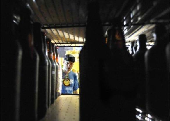 Dan Stewart peers into a cooler of New Belgium Brewing bombers as he shops Saturday (Photo Credit: The Coloradoan/ Dawn Madura)