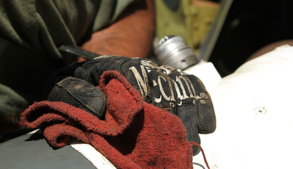 A gloved hand wipes down a component on a military helicopter to keep equipment clean.  An estimated 90,549 facilities in 13 economic sub-sectors generate solvent contaminated wipes.